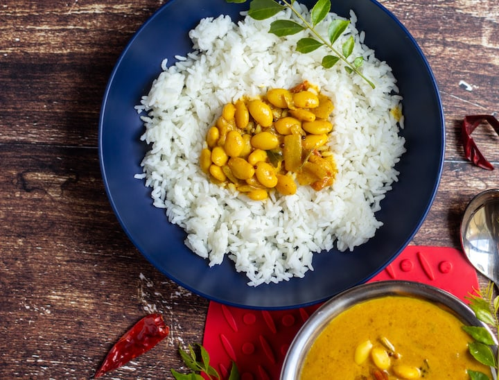 top angle shot of mochai kuzhambu with rice in a blue bowl
