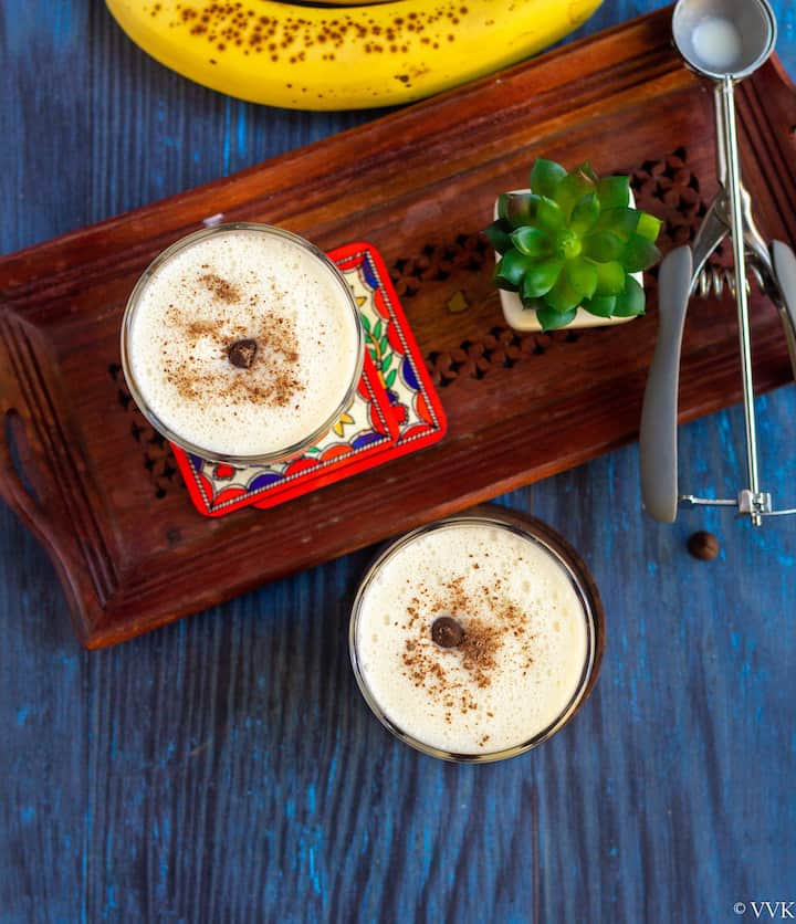 overhead shot of banana milkshake with grated chocolate on top with a succulent on the side as a prop