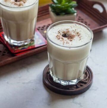 banana milkshake in a glass cup garnished with grated chocolate