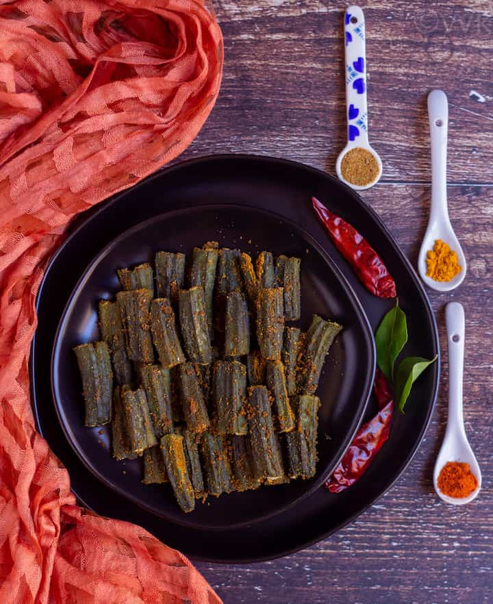 overhead shot of stuffed and baked okra placed on black plate with assorted spices on the side