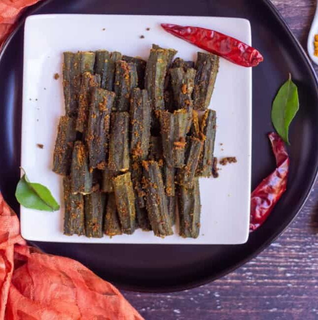 stuffed okra place on a white plate with dried red chilies on the side