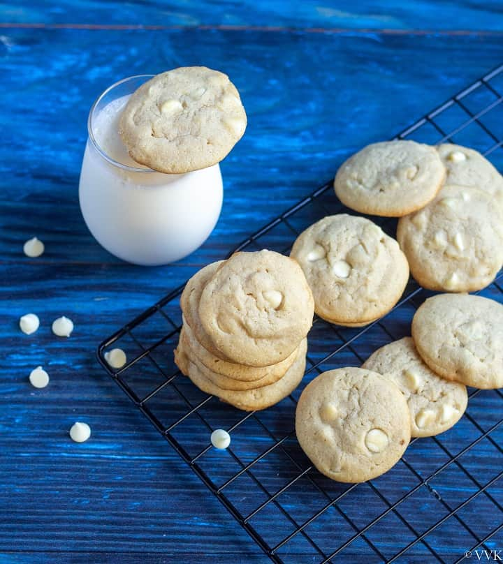 stack of white chocolate chip cookies on a cooling rack with a glass of milk on the side
