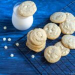 square image of eggless white chocolate chip cookies with macadamia nuts placed on a cooling rack