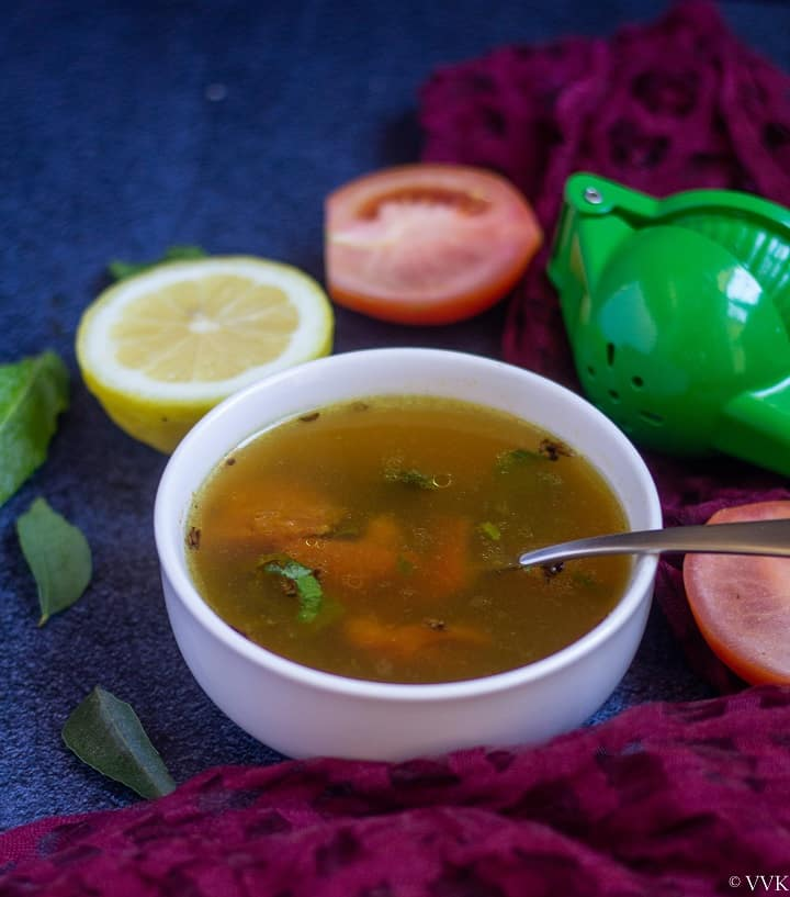 south indian style lemon broth served in a white bowl with a spoon inside