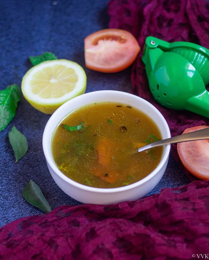 lemon rasam in a white bowl with a spoon in with some tomato slices and lemon wedges on the side