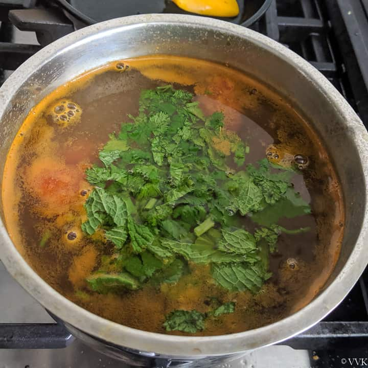 adding herbs to the rasam