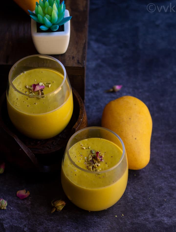 mango lassi in two glass jars with a mango on the side