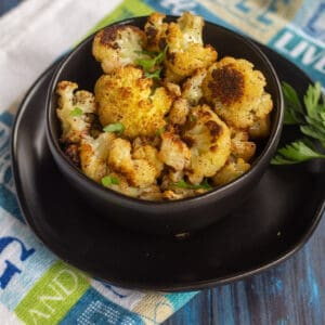 roasted cauliflower in a black bowl with parsley