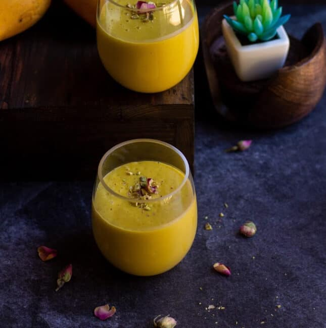 square image of mango lassi in two jars with a artificial succulent on the back as a prop