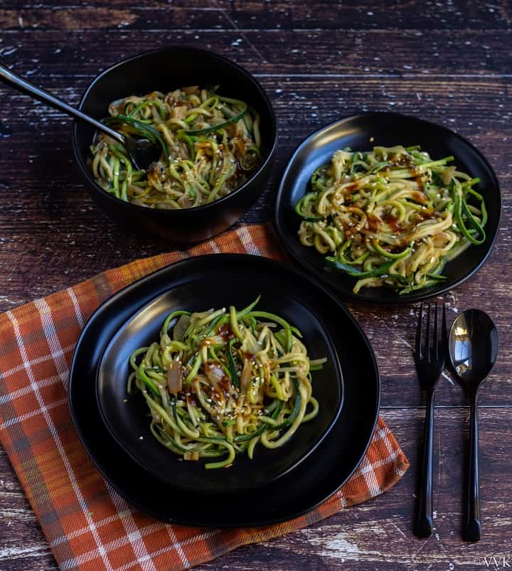 angled shot of zucchini noodles in a blackserveware