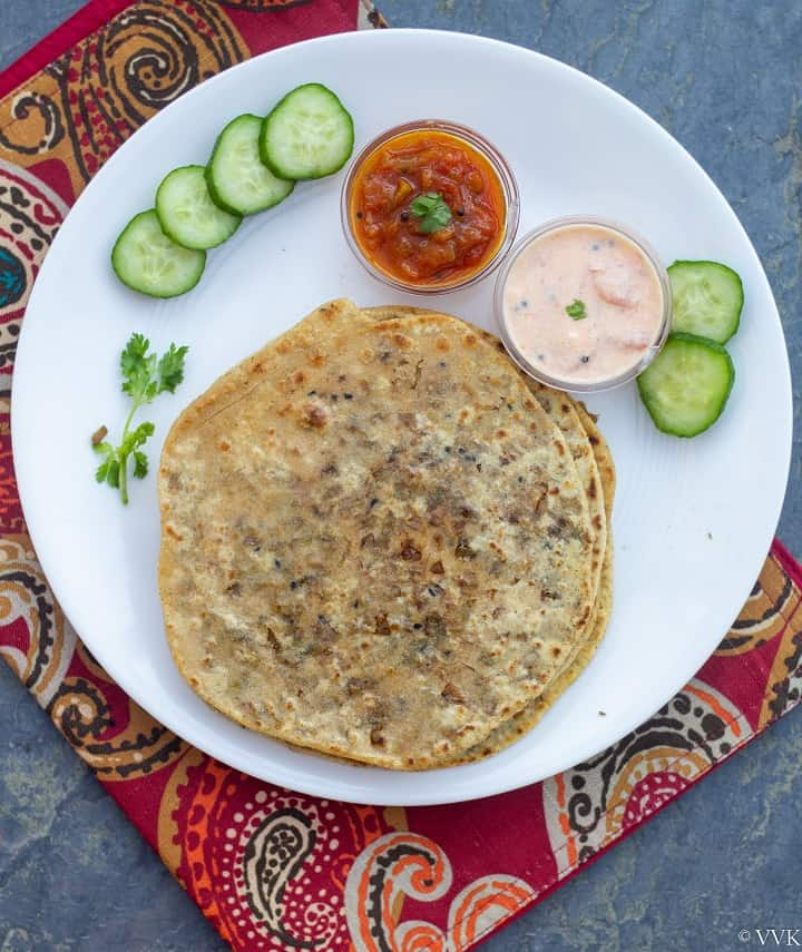 overhead shot of brussels sprouts paratha with tomato relish and raita