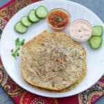square image of brussels srouts stuffed paratha in white plate with raita and relish