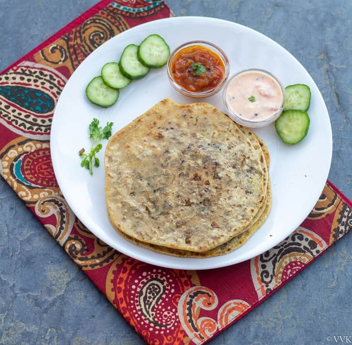 brussels srouts stuffed paratha in white plate with raita and relish with cucumbers placed on a red mat