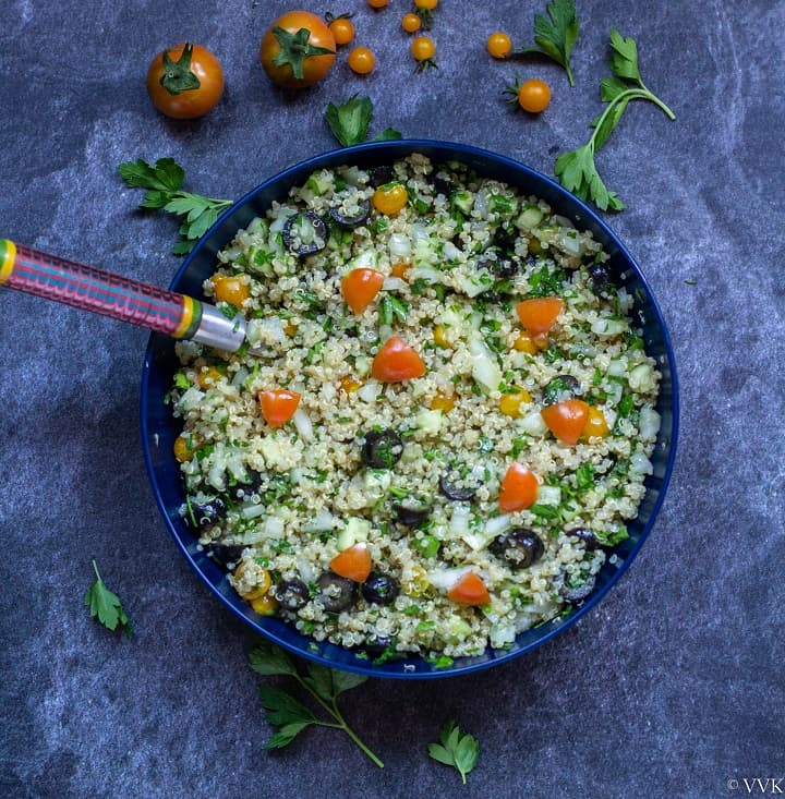 simple quinoa tabbouleh salad in blue bowl with some cherry tomatoes and herbs on the side