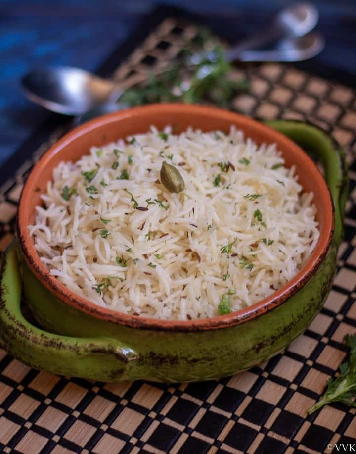simple and easy jeera rice served in a terracotta serveware placed on a striped mat