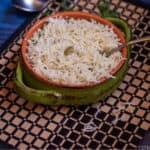 square image of jeera rice made in instant pot served in a terracotta bowl