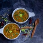 square image of leeks sambar in white bowls with wooden spoon on the side