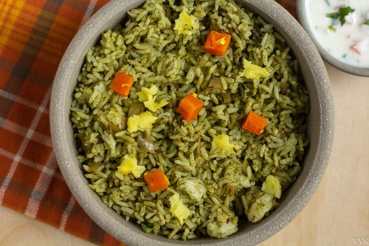 close up shot of mint rice topped with carrots and potatoes