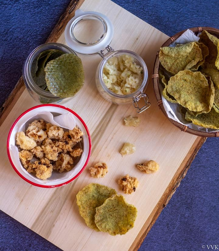 overhead shot of green and onion fryums fried and dried placed on a wooden board