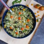 square image of quinoa tabbouleh served in a blue bowl