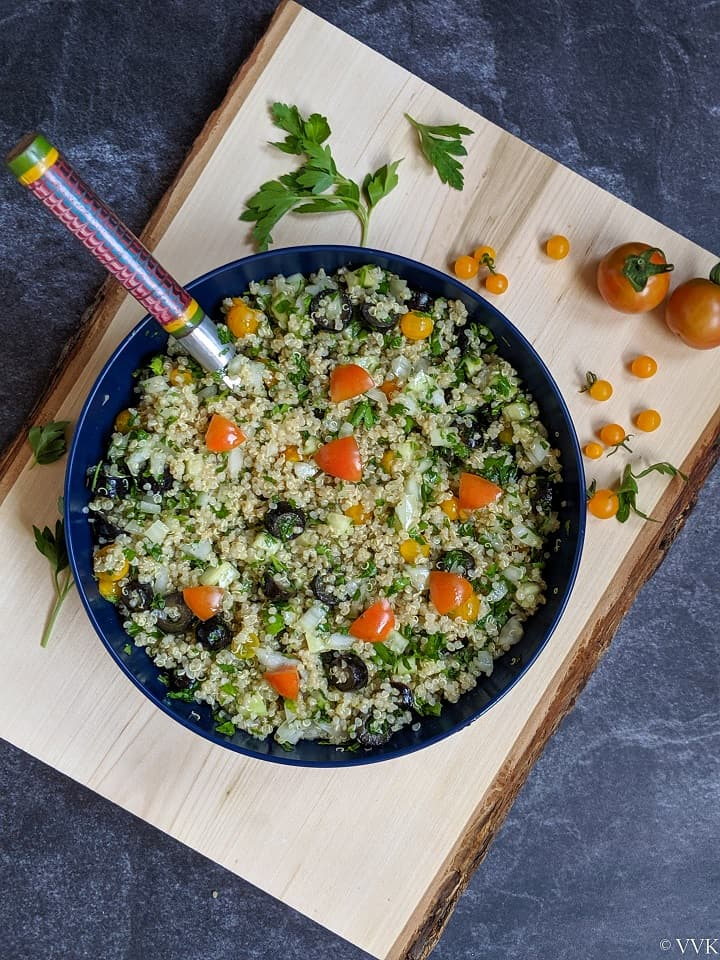 overhead shot of quinoa tabbouleh in a blue serving bowl placed on a wooden board