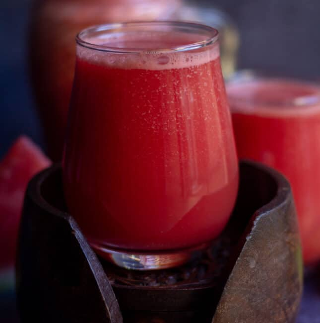 square image of watermelon ginger juice in a glass jar placed on a wooden coasted