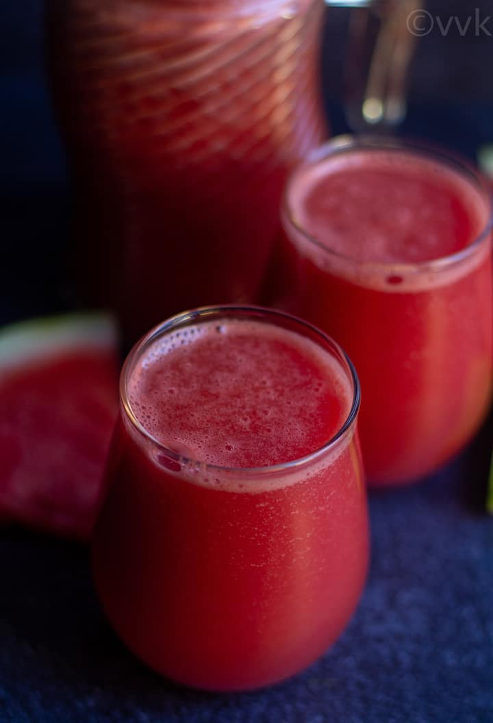 close up shot of watermelon ginger juice in two glasses with a watermelon wedge on the side
