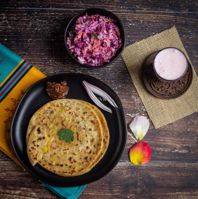 overhead shot of paratha platter with aloo paratha, lemon pickle, coleslaw and lassi