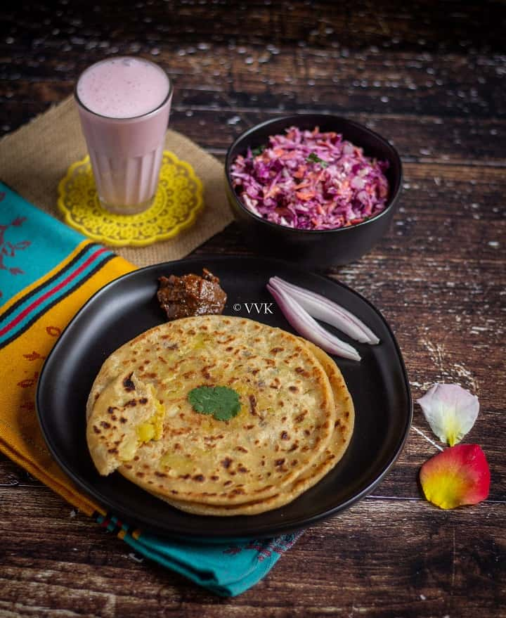 aloo paratha spread with aloo paratha, cabbage coleslaw, lassi and lemon pickle