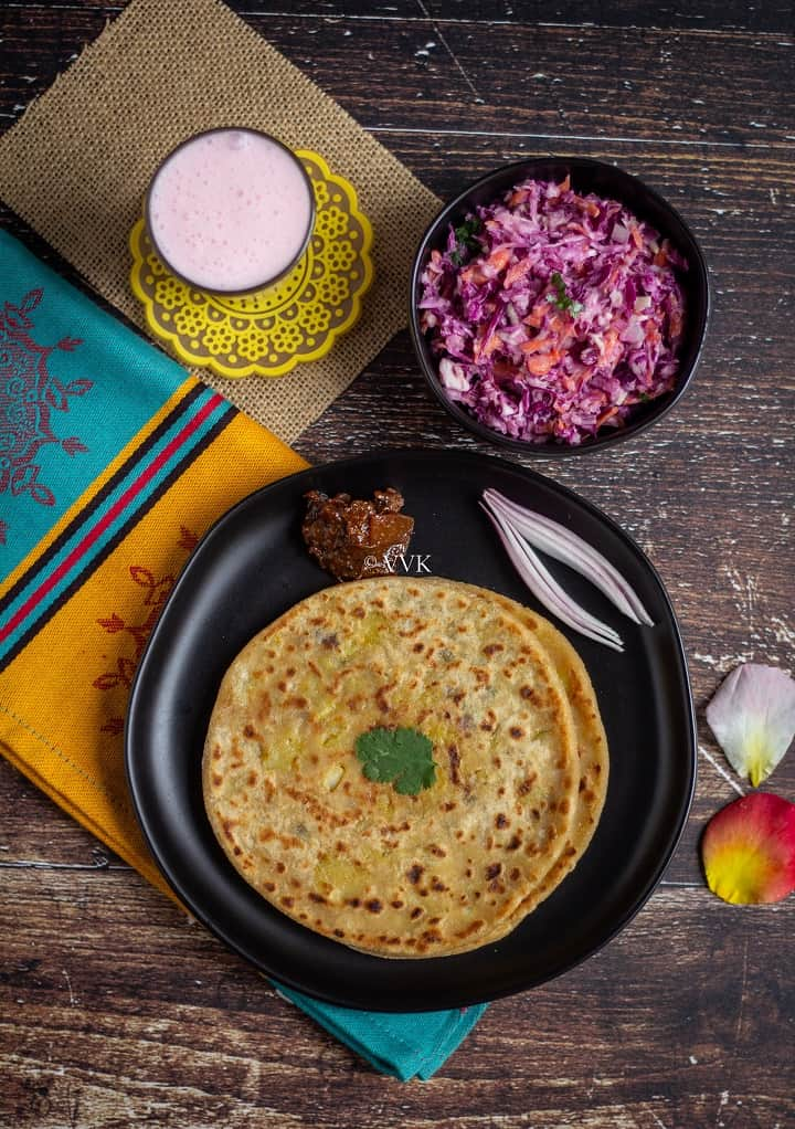 overhead length image shot of paratha thali with aloo paratha, lassi, salad and pickle