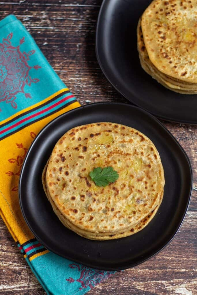 simple aloo paratha stacked up on the black plate with a cilantro leaf on top