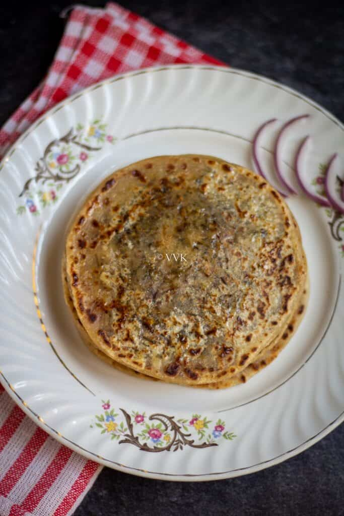 close up shot of cheese paratha in a white plate with onion slices on the side