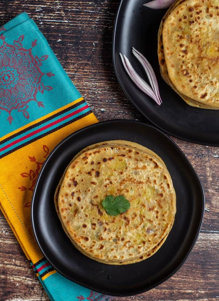 aloo paratha stacked and placed on a black plate