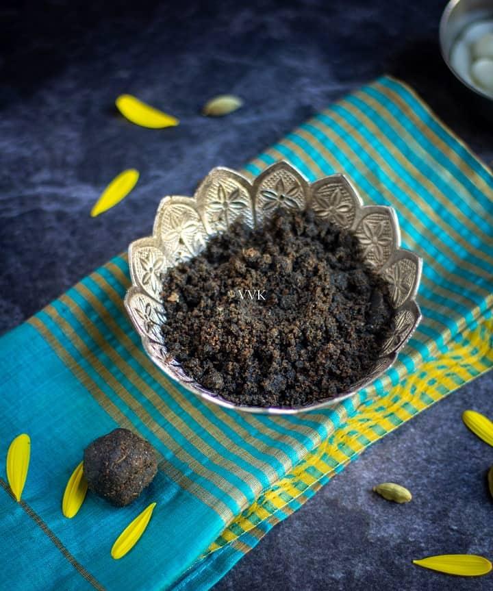 easy sesame seed laddu in silverware placed on a green silk fabric