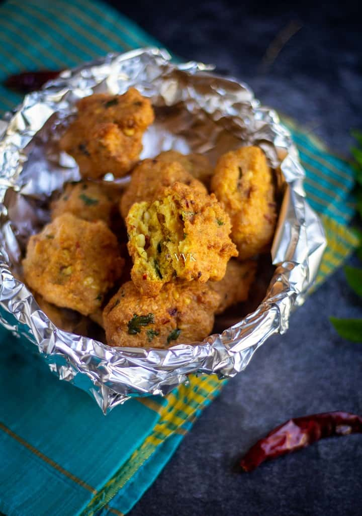 paruppu vadai in a basket wrapped with foil with one cut into two