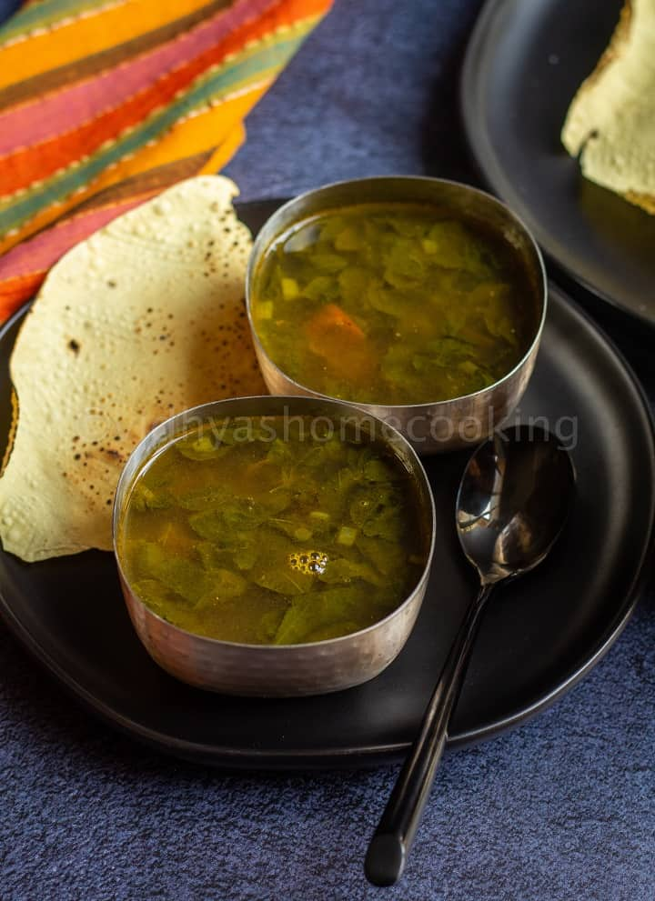 moringa rasam served in two silverwares with papad on the side