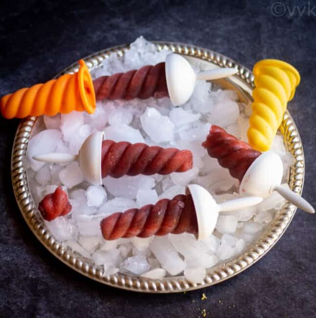 square image of kala khatta popsciles on a plate with ice