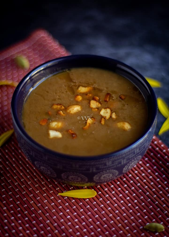 easy pasi paruppu payasam served in a blue bowl with cashew tempering placed on a red mat