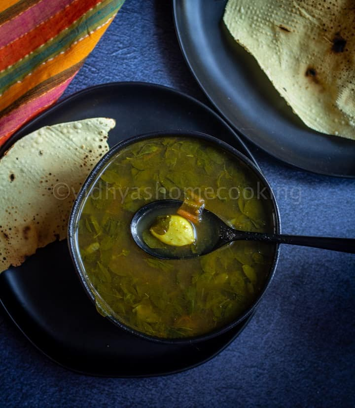 murungai keerai rasam served in black bowl with papad on the side with a spoon inside with garlic