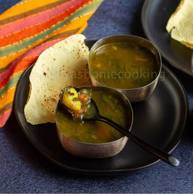 square image of moringa rasam served in two silver ware