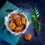 square image of paruppu vadai without onions blaced in a bowl with curryleaves on the side
