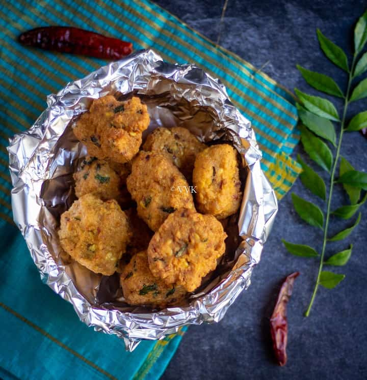 paruppu vadai placed in a foil wrapped basket with curry leaves and dried red chilies on the side