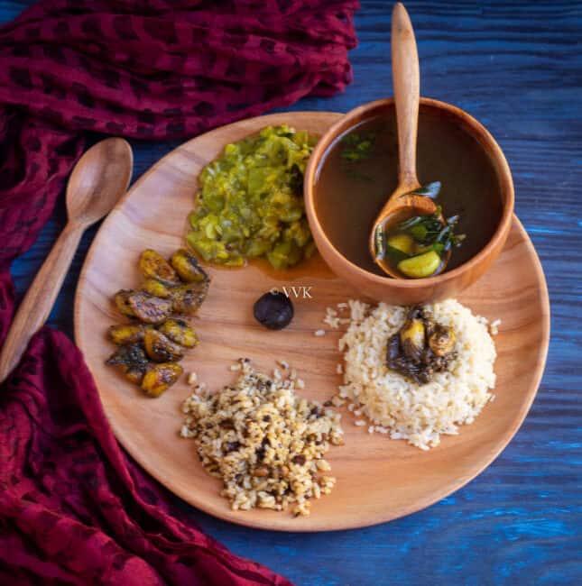 square image of pathiya sapadu with rice, milagu kuzhambu, kootu and rasam served on neem wood plate