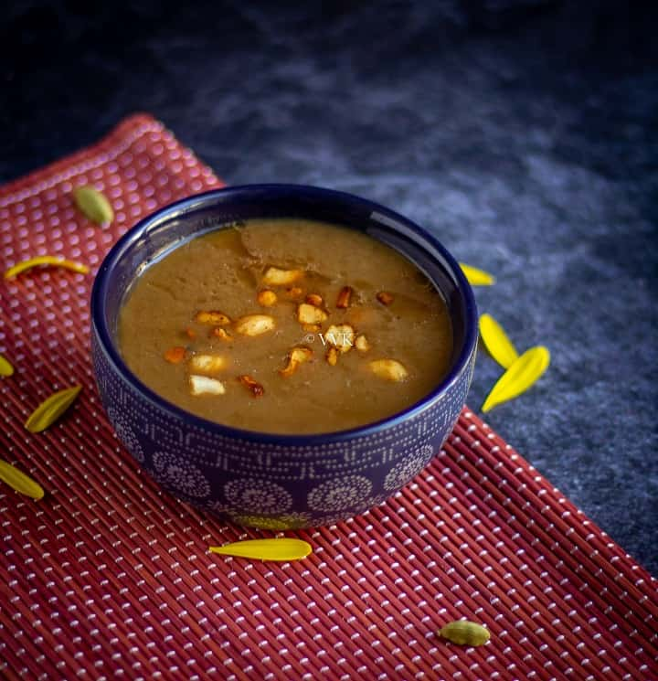 pasi paruppu payasam served in a blue bowl placed on a red mat with flower petals on the side