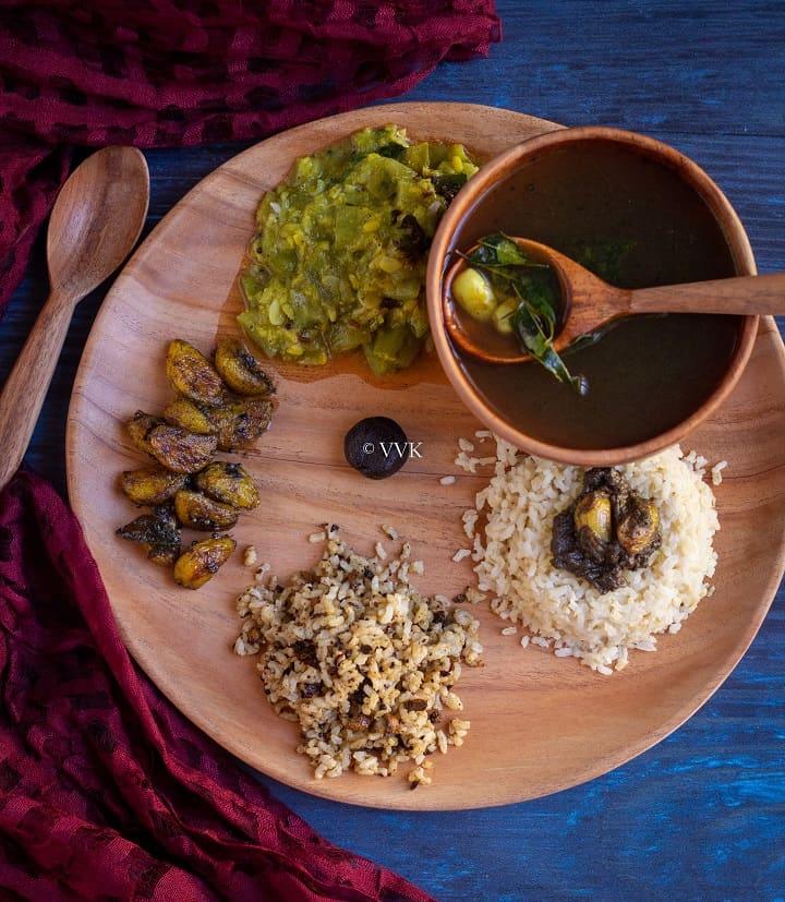 overhead shot of pathiya sapadu with rice, milagu kuzhambu, kootu and rasam served on neem wood plate