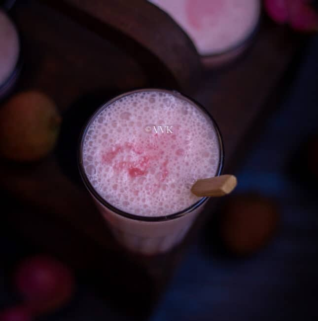 square shot of lychee lassi with wooden spoon inside