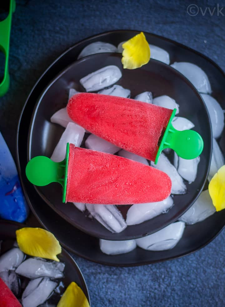 overhead shot of two rose syrup and rooh hafza popsicles placed on black plate