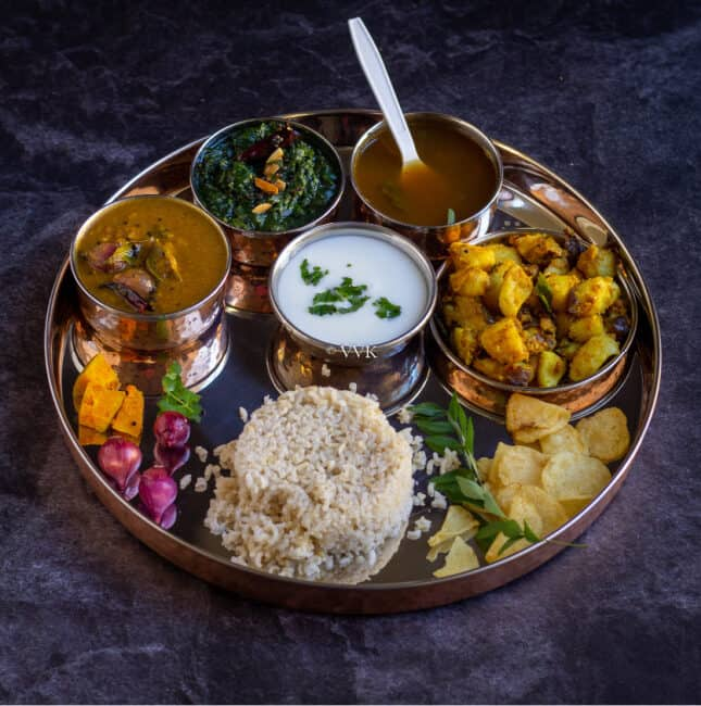 square image of south indian lunch thali with sambar, rasam, potato