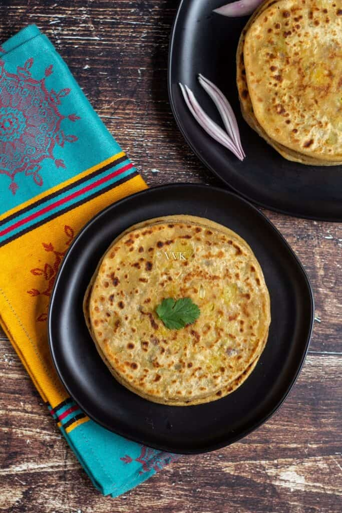 aloo paratha stacked up in black plates with onion wedges on one plate and cilantro on the other