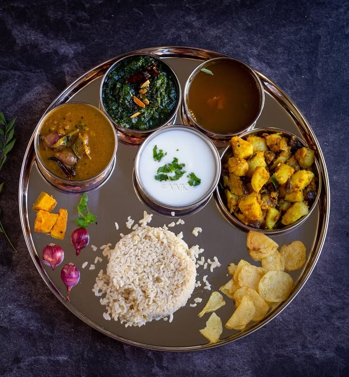 overhead shot of south indian lunch menu with sambar, rasam, kootu and curry